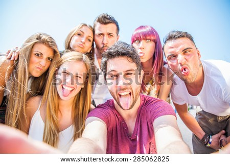 Group of friends grimacing in front of the camera - Young happy people having fun at party and making funny faces while photographing themselves - stock photo