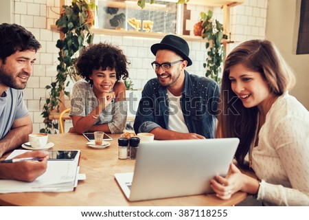 Group of friends hanging out in a coffee shop with a laptop amongst them. Happy young people sitting at restaurant using laptop computer. - stock photo
