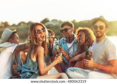 Group of friends hanging out with beer at the beach