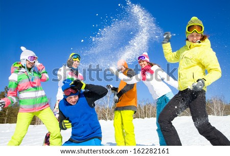 group of friends have a snowball fight - stock photo