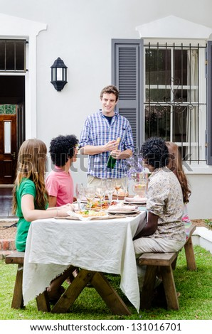 Group of friends having a gathering party, celebrating a special occasion with speech and champagne, sitting around a table with plenty of food - stock photo