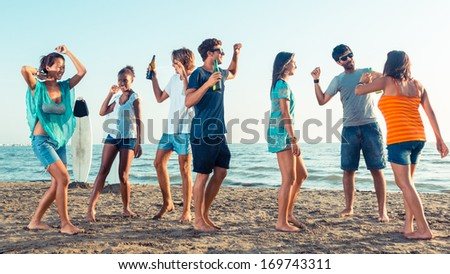 Group of Friends Having a Party on the Beach - stock photo