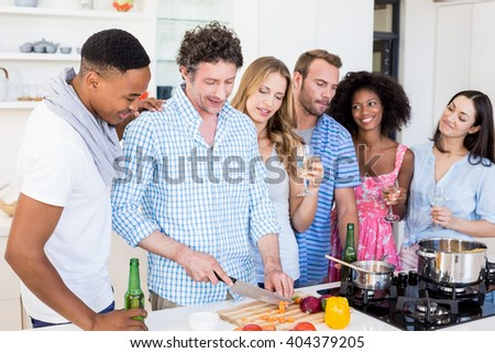 Group of friends having alcoholic beverage and preparing meal in kitchen at home - stock photo