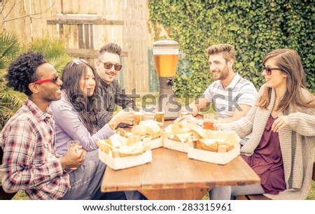 group of friends having brunch together. sitting in the garden and drinking beer. Burgers and friets are on the table. concept about friendship - stock photo
