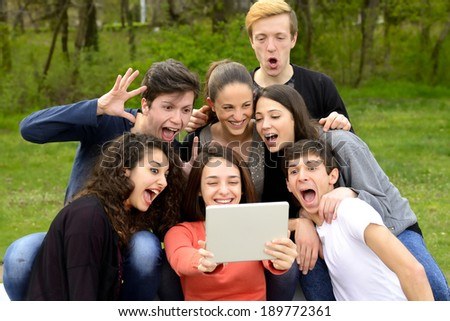 Group of friends having fun and goofing around while using a tablet in a park - stock photo
