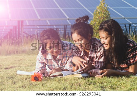Group of friends having fun and reading on the grass. Solar power plant in the background.Solar Energy ,The concepts of Clean Energy.