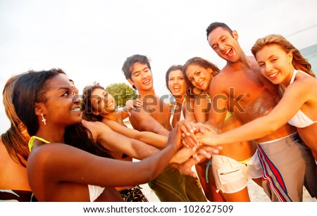 Group of friends having fun and smiling at the beach