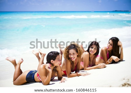Group of friends having fun at a tropical beach  - stock photo