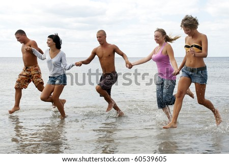 Group of friends having fun at the beach - stock photo