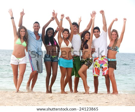 group of friends having fun at the beach with their arms up - stock photo