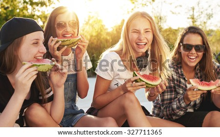 Group of friends having fun eating water melon outside - stock photo