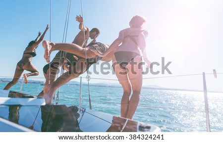 Group of friends having fun jumping and diving into the blue water - stock photo