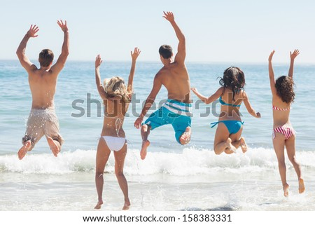 Group of friends having fun on the beach back to camera on holidays