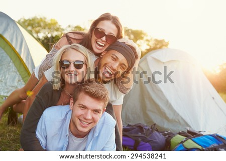 Group Of Friends Having Fun Outside Tents On Camping Holiday - stock photo