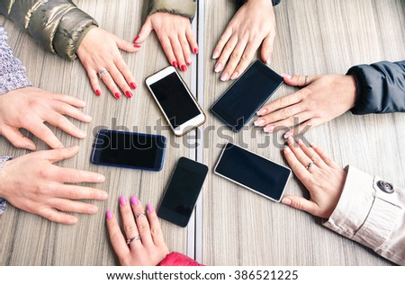 Group of friends having fun together with smartphones - Closeup of hands social networking with mobile cellphones - Technology and phone addiction concept on wood background - Focus on mobile phones - stock photo