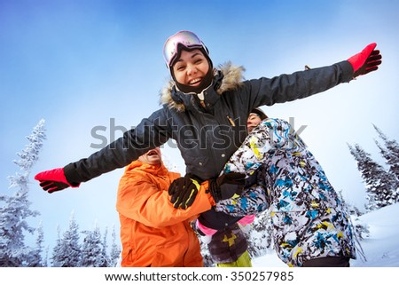 Group of friends having fun tosses girl by hands. Sheregesh resort, Siberia, Russia - stock photo