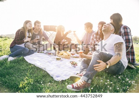 Group of friends having fun while eating and drinking at a pic-nic - Happy people at bbq party - stock photo
