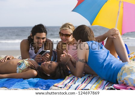 Group of friends having fun while lying on the beach - stock photo
