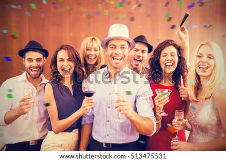 Group of friends having fun while standing with drinks against flying colours