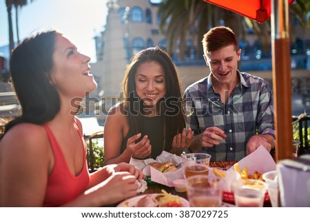 group of friends having great time eating lunch together outside under summer sun