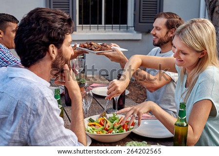 group of friends having outdoor garden barbecue salad dinner with drinks - stock photo