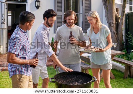 group of friends having outdoor garden barbecue with alcoholic beer drinks - stock photo
