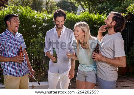 group of friends having outdoor garden party with alcoholic beer drinks - stock photo
