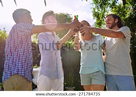 group of friends having outdoor garden party with alcoholic beer drinks