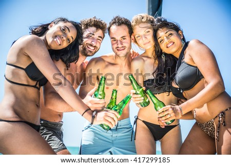 Group of friends having party and toasting beer bottles - Four cheerful people enjoying summer vacation