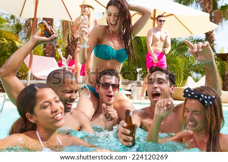 Group Of Friends Having Party In Pool Drinking Champagne - stock photo