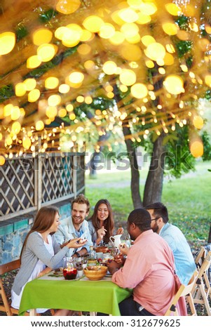 Group of friends having traditional Thanksgiving dinner outdoors - stock photo