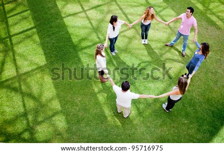 Group of friends holding hands in a circle - outdoors - stock photo