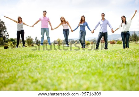 Group of friends holding hands outdoors having fun - stock photo