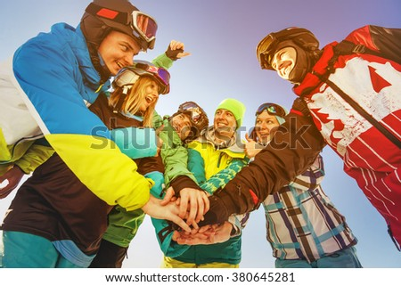 Group of friends holding their hands like good team. Sheregesh resort, Siberia, Russia - stock photo