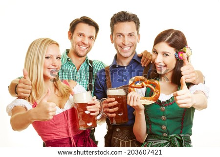 Group of friends holding thumbs up in Bavaria with beer and pretzel - stock photo