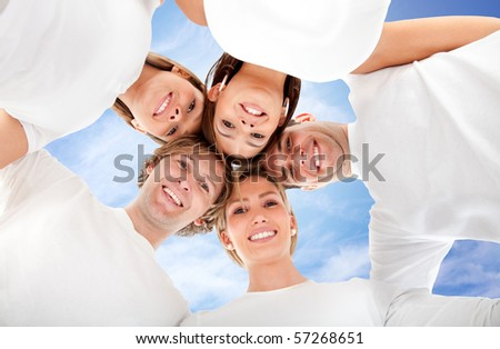 Group of friends hugging with the sky on the background