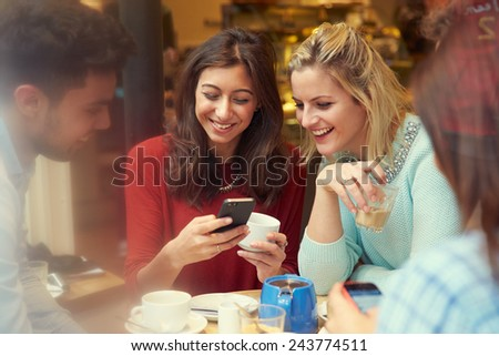 Group Of Friends In Caf�¢?? Using Mobile Phones - stock photo