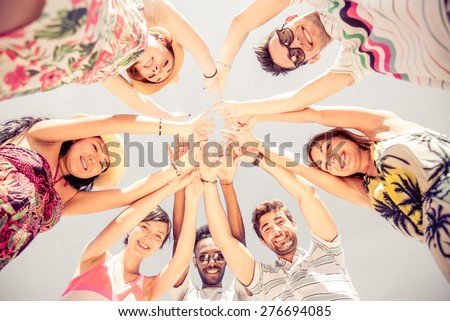Group of friends in circle looking down and rising hands - Several people exulting on the beach at sunset - Concepts about summer,lifestyle and happiness - stock photo