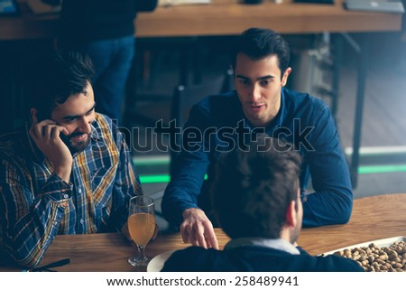 Group Of Friends In Pub Having Fun And Drinking Beer