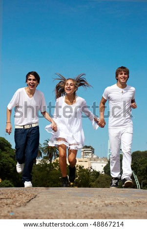 Group of friends in running along the street against a city and the sky - stock photo