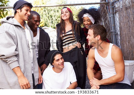 Group Of Friends In Urban Setting Standing By Fence