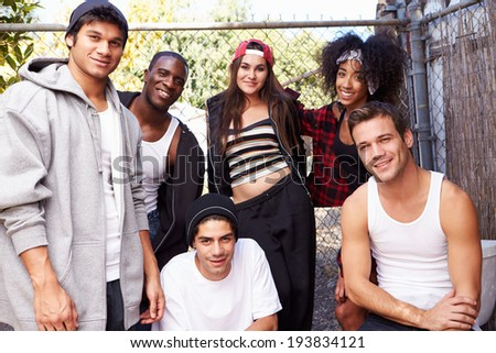 Group Of Friends In Urban Setting Standing By Fence - stock photo