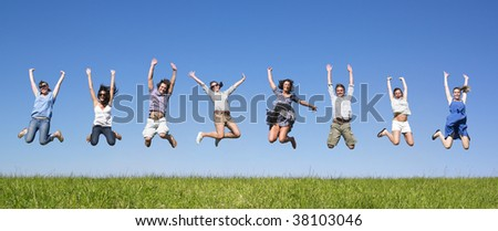 Group of friends Jumping in meadow under blue sky - stock photo