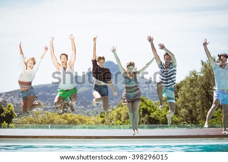 Group of friends jumping in swimming pool with their hands raised - stock photo