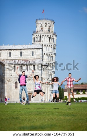 Group of Friends Jumping with Pisa Leaning Tower on Background - stock photo