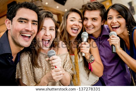 Group of friends karaoke singing at the bar