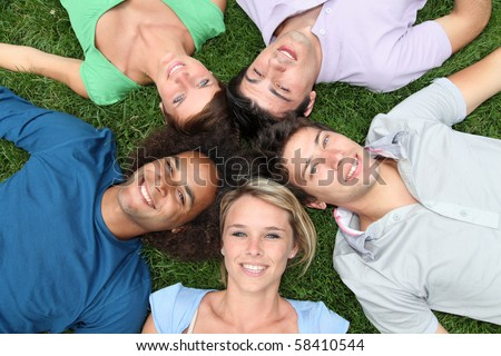 Group of friends laying down in park - stock photo