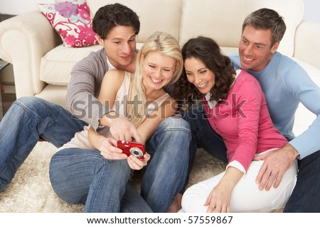Group Of  Friends Looking At Pictures On Digital Camera At Home - stock photo