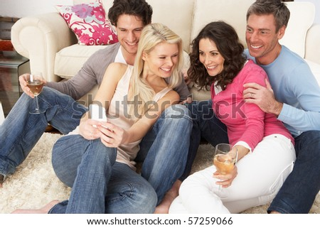 Group Of  Friends Looking At Pictures On Smartphone At Home - stock photo