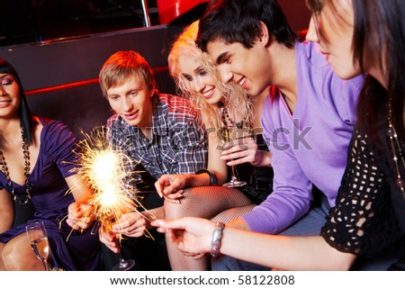 Group of friends looking at sparkling Bengal lights during party - stock photo